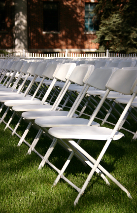 white folding plastic with metal chairs set up on grass